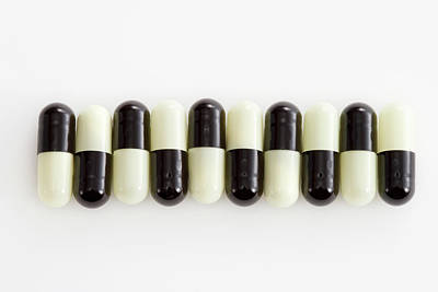 Healthcare And Medicine Photograph - Row Of Black And White Pills by Schedivy Pictures Inc.