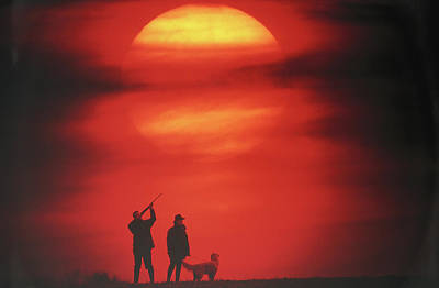 Silhouette Of Couple With Dog, Man Aiming, Sunset Art Print by David De Lossy