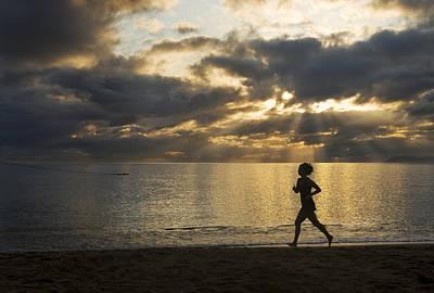 Silhouetted Woman Jogging On A Beach Art Print by Mattias Klum