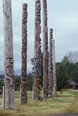 Amerindian Photograph - Six Wooden Totem Poles Stand In A Row by Stephen Sharnoff