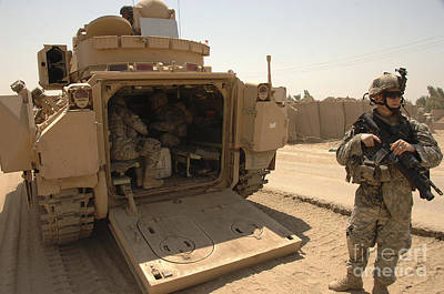 Armored Vehicle Photograph - Soldiers Climb Into The Back Of A M2 by Stocktrek Images