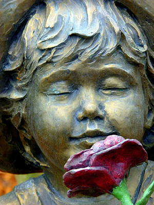 Photograph - Statue Of Child Smelling Red Rose by Jeff Lowe