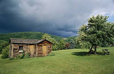 Storm Clouds Form Above A Log Cabin Art Print by Raymond Gehman