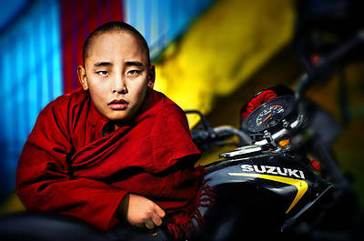 The Boy Monk In Red Robe Standing Beside A Motorcycle In A Buddh Art Print by Max Drukpa