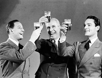 Three Men Making Toast With Glasses Of Beer (b&w) Art Print by Hulton Archive