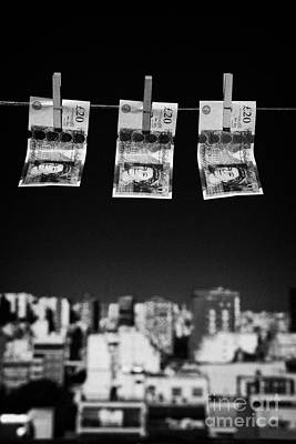 Three Twenty Pounds Sterling Banknotes Hanging On A Washing Line With Blue Sky Above A City Skyline Art Print by Joe Fox