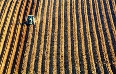 Tractor Plowing A Field Art Print by John Short