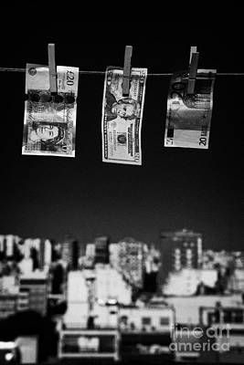 Sterling Photograph - Twenty Pounds Dollars Euro Banknotes Hanging On A Washing Line With Blue Sky Over City Skyline by Joe Fox
