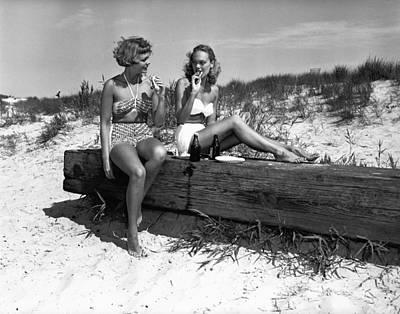 Two Women In Bikini Eating Snack On Beach, (b&w) Art Print by George Marks