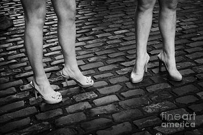 Two Young Women Wearing High Heeled Shoes And Fake Tan On Cobblestones On A Night Out In Dublin  Art Print by Joe Fox