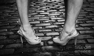 Two Young Women Wearing High Heeled Shoes And Fake Tan On Cobblestones On A Night Out Art Print by Joe Fox