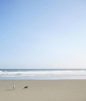 Woman And Dog On Beach Art Print by Richard Newstead