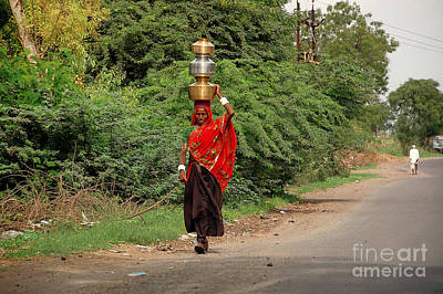 Photograph - Woman Carrying Water by Charuhas Images