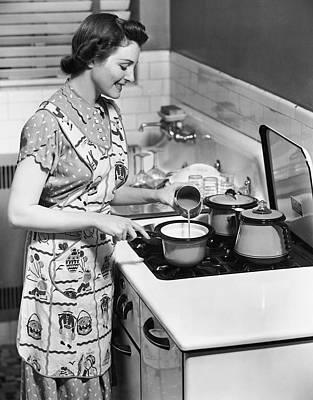 Woman Preparing Food On Stove Art Print by George Marks