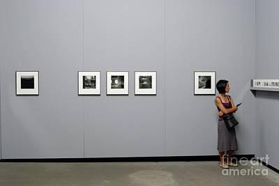 Woman Watching Photos At Exhibition Print by Sami Sarkis