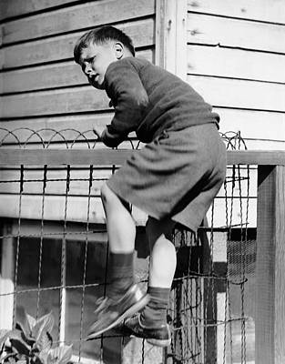 Young Boy Climbing Fence Art Print by George Marks