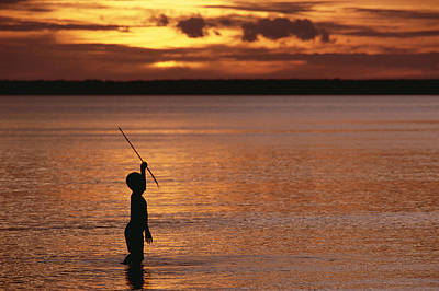 Young Boy Spear Fishing At Sunset Art Print