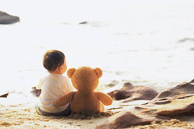 Photograph - Baby And Teddy Bear Sit Togather On The Beach by Anek Suwannaphoom