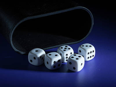 Sports Royalty-Free and Rights-Managed Images - Five white dices and a cup lying on a table by Stefan Rotter