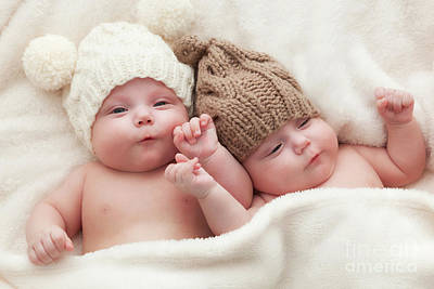 Adorable Photograph - Twin Sisters Babies Lying Together Wearing Funny Woolen Bobble Hats by Michal Bednarek