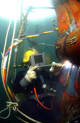 U.s. Navy Diver Welds A Repair Patch Art Print by Stocktrek Images