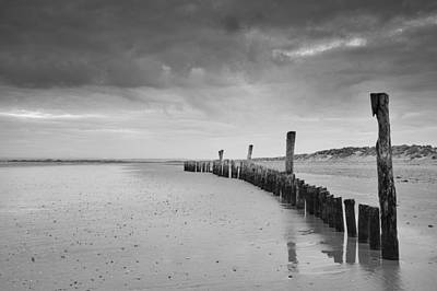 Black And White Wooden Posts On Beach With Stormy Sky Art Print by Matthew Gibson