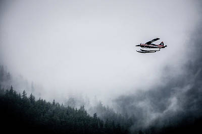 Photograph - Single Prop Airplane Pontoon Plane Flying Through Fog Over Alask by Alex Grichenko