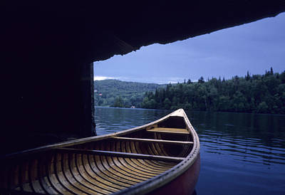 Swim Ladder Photograph - A Canoe Sticks Out Of A Boathouse On An by Taylor S. Kennedy