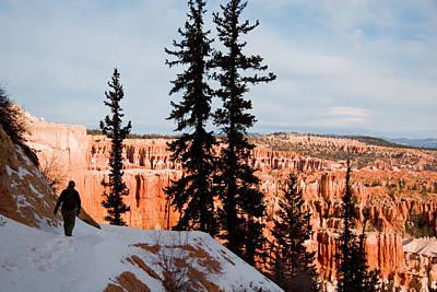 A Hiker Walks Along A Ledge In Winter Art Print by Taylor S. Kennedy