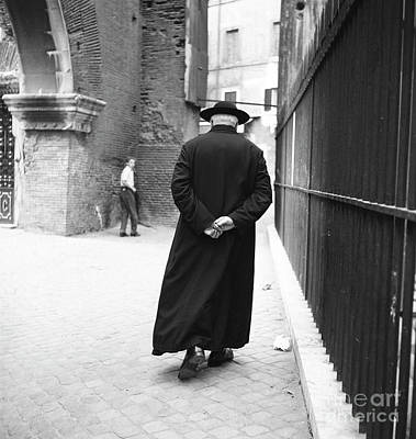Priests Photograph - A Priest Walks Down A Street In Rome, 1955 by The Harrington Collection