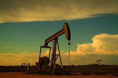 Birds Rights Managed Images - A pump jack and clouds Artesia New Mexico Royalty-Free Image by Jeff Swan