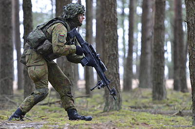 Photograph - A Soldier Steps Cautiously Through A Lithuanian Forest by Paul Fearn
