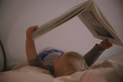 A Toddler Looks At A Book While Lying Print by Roy Gumpel