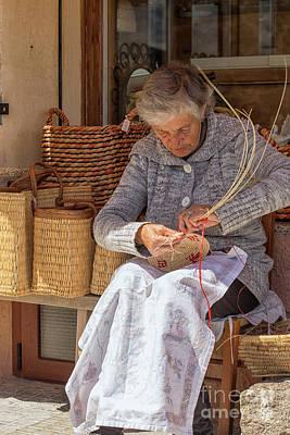 Photograph - A Woman Weaving A Basket In Castelsardo by Patricia Hofmeester
