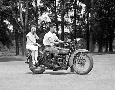 1920s Fashion Photograph - A Young Man Drives A  Motorcycle While by Everett