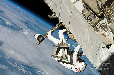 Photograph - An Astronaut Crawls Along A Truss by Stocktrek Images