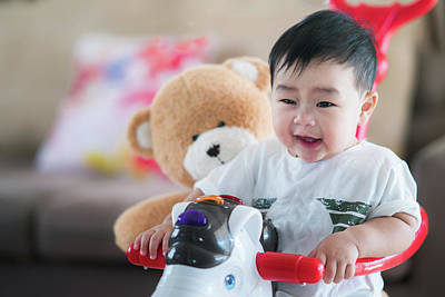 Photograph - Asian Baby And Teddy Bear Play A Bicycle Toy by Anek Suwannaphoom