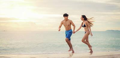 Family Beach Wedding Wall Art - Photograph - Asian Couple Run Togather On The Beach  by Anek Suwannaphoom