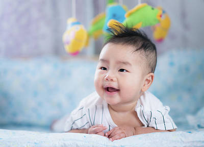 Photograph - Asian Newborn Baby Smile In A Bed With Fish And Animal Mobile by Anek Suwannaphoom