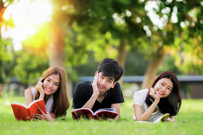 Photograph - Asian Student And Friend Relax And Read A Book In University by Anek Suwannaphoom