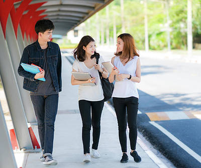 Photograph - Asian Student In University Play, Walk And Talk Together On The Walkway by Anek Suwannaphoom