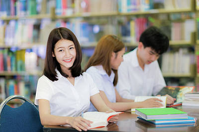 Photograph - Asian Student Lady Smile And Read A Book In Library In Universit by Anek Suwannaphoom