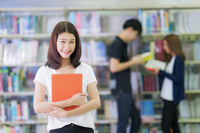 Photograph - Asian Student Lady Smile And Read A Book In Library In University With Her Friends by Anek Suwannaphoom