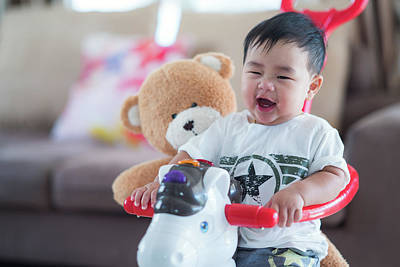 Photograph - Baby And Teddy Bear Play A Bycycle Toy by Anek Suwannaphoom