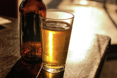 Backlit Glass Of Beer And Empty Bottle On Table Art Print