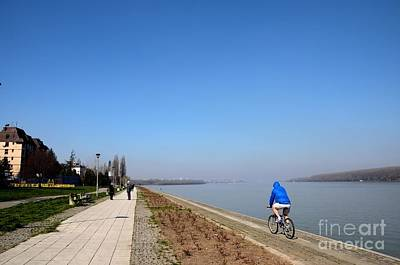 Photograph - Bicyclist And Senior Couple At Bank Of Sava River Belgrade Serbia by Imran Ahmed
