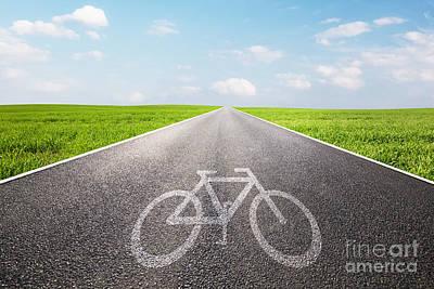 Direction Photograph - Bike Symbol On Long Straight Asphalt Road by Michal Bednarek