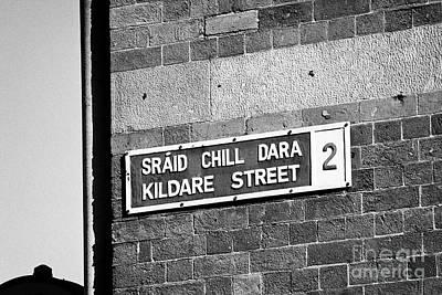 Bilingual Street Signs Photograph - blue and white bilingual english irish street sign for kildare street in Dublin Republic of Ireland by Joe Fox