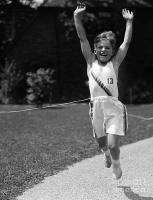 Boy In Track Uniform Crossing Finish Art Print by H. Armstrong Roberts/ClassicStock