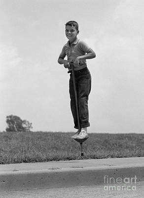 Boy Jumping On Pogo Stick, C.1960s Print by H. Armstrong Roberts/ClassicStock
